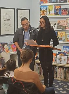 Stephen Lin helps Marina Fec read their question-answer poetry at White Whale Bookstore.